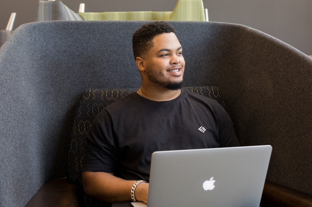 Man sits in chair, smiling at something off camera, with laptop open in front of him