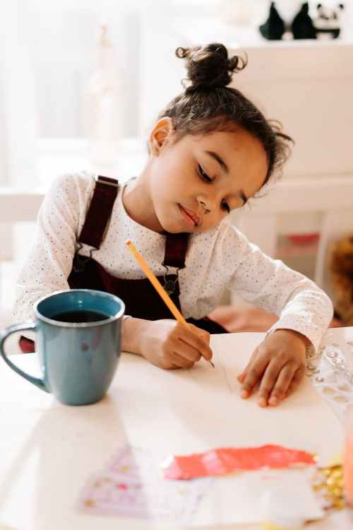 Young girl draws on white paper with a pencil