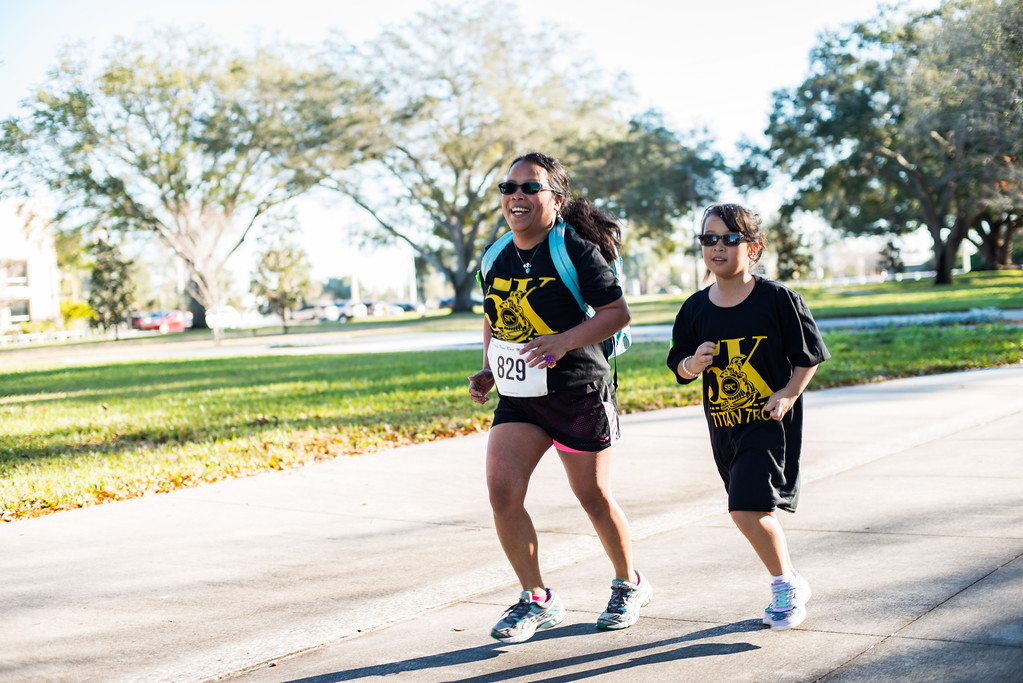 Woman and child wearing 5K Titan Trot shirts run together at last year's event.