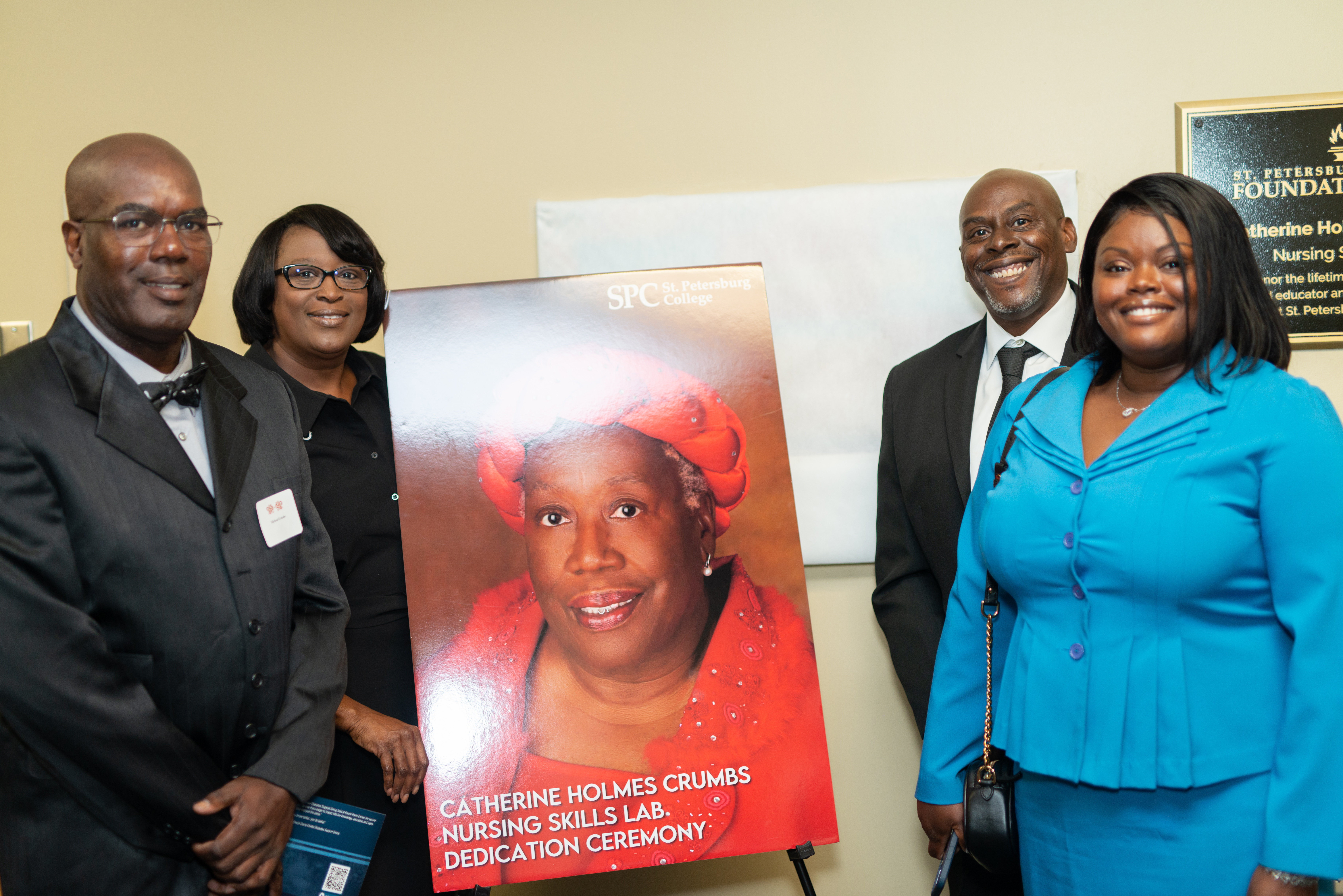 Four people including Dr. Williams stand next to a poster featuring the smiling face of Catherine Holmes Crumbs.
