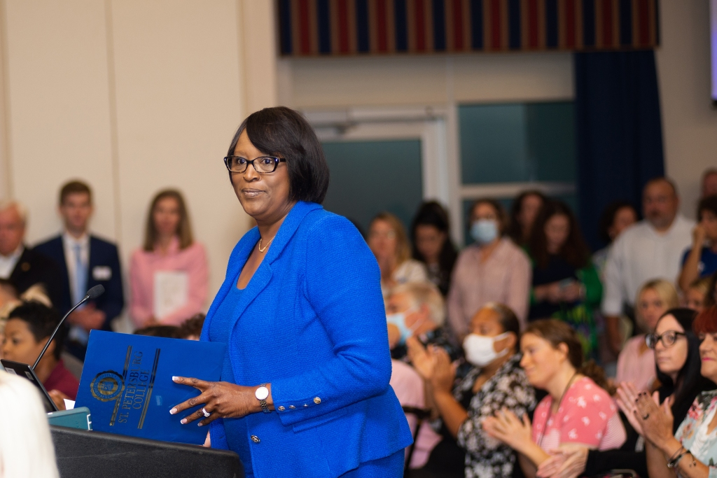 Dr. Williams wears a blue dress suit while standing at a podium in front of a large group of people.