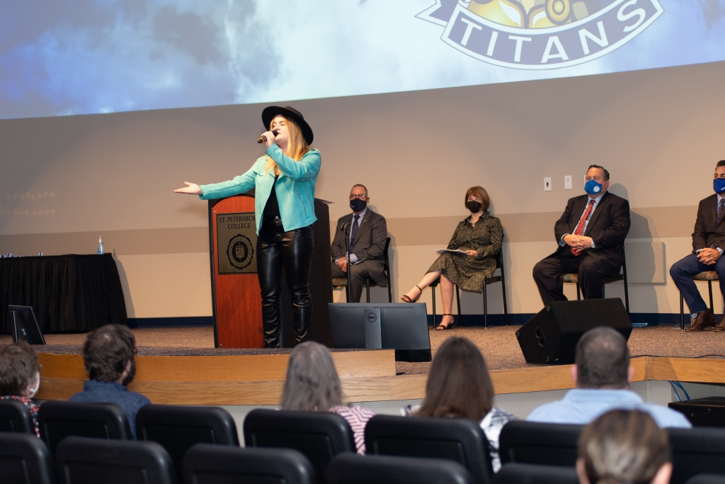 SPC alumni Cierra Reynolds sings on stage while wearing black pants, a blue blazer, and black broad-rimmed hat. She holds a mic while singing.