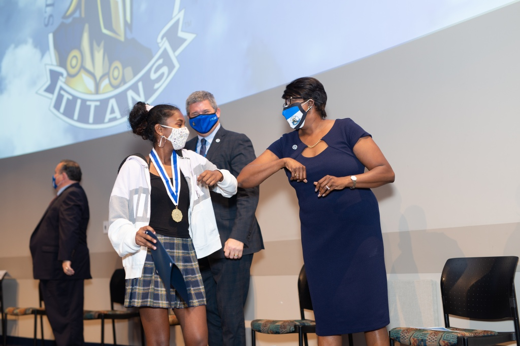Dr. Williams bumps elbows with a young Presidential Scholar to congratulate her as she walks across the stage.