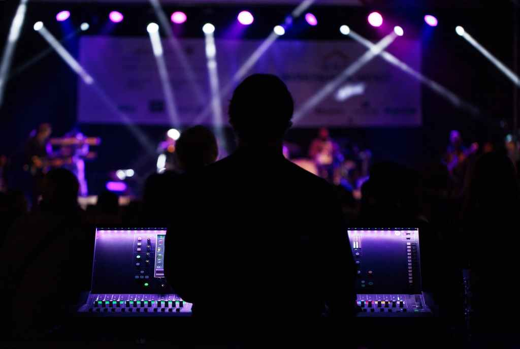sound engineer stands behind the board facing the stage awash in purple lighting